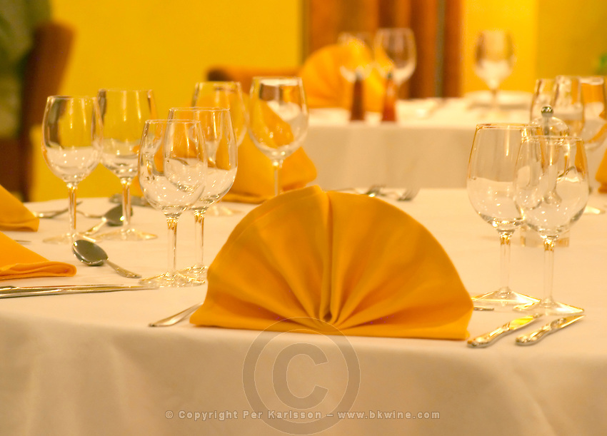 A dining table with napkins knives and forks wine glasses and white linen table cloth at the restaurant at the hotel Pavillon de l'Hermitage. Tain l'Hermitage, Drome, Drôme, France, Europe