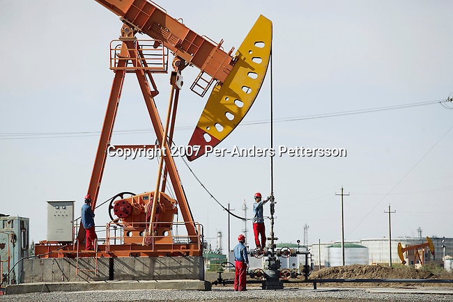 TAZHONG, CHINA - JUNE 15: Workers survey an oil well in an oil field on June 15, 2007 in Tazhong, Xinjiang Province, China. China is the second largest oil consuming country after the US. China's oil fields produce about 3.2 million barrels a day and they consume about 6.5 million a day. (Photo by Per-Anders Pettersson)..