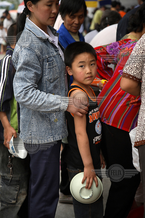 Displaced children wait for food at a temporary shelter at the Jiuzhou Stadium in Mianyang. On the 12/05/2008 an earthquake measuring 8.0 on the Richter scale hit the province of Sichuan.