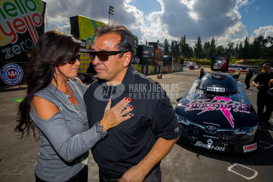 Nov 15, 2015; Pomona, CA, USA; NHRA funny car driver Tony Pedregon (right) cries as he embraces wife Andra Pedregon following the final run of his career during the Auto Club Finals at Auto Club Raceway at Pomona. Mandatory Credit: Mark J. Rebilas-USA TODAY Sports