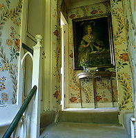 A grand portrait hangs on the landing at the top of the narrow staircase against a floral wall paper