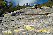 A hiker ascending South Slide, which is located along Mt. Tripyramid Trail just pass Kate Sleeper Trail junction in the White Mountains, New Hampshire USA. Trail blazing is painted on the rock in the foreground to indicate directions of trails.