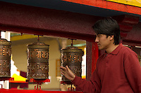 Buddhist devotee turning the prayer wheels at a monastery, Sikkim, India