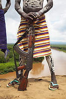 Ethiopia. Southern Nations, Nationalities, and Peoples' Region. Omo Valley. Korcho Village. Kara tribe. Agro-pastoralist group. A Kara warrior stands his Kalashnikov close to the Omo river. The Kara men are best known for the elaborate body painting they indulge in before important ceremonies. They paint their faces and bodies in white chalk. Scarification plays an important role in Kara body decoration. The AK-47 (also known as the Kalashnikov, AK, or Kalash) is a selective-fire (semi-automatic and automatic) assault rifle. The Omo Valley, situated in Africa's Great Rift Valley, is home to an estimated 200,000 indigenous peoples who have lived there for millennia. Amongst them are 1,000 to 2,000 Karo who dwell on the eastern banks of the Omo river. Southern Nations, Nationalities, and Peoples' Region (often abbreviated as SNNPR) is one of the nine ethnic divisions of Ethiopia. 8.11.15 © 2015 Didier Ruef
