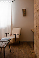 The textures of the wood floorboards and furnishings contrast with the bare white walls of the bedroom