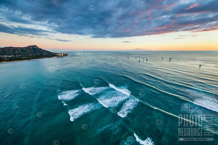 An aerial perspective of surfers in Waikiki, with Diamond Head to the distant left and sailboats to the right, Honolulu, O'ahu.