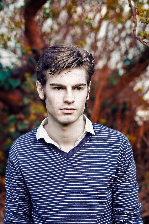 Young pale-skinned man wearing a blue striped shirt looking away with colourful garden background.