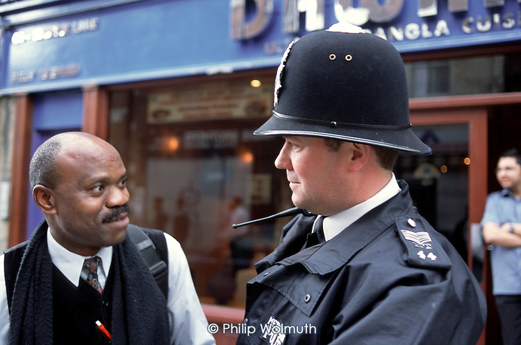 Sergeant Simpson, based  in the Brick Lane police office, talks to a local resident while on patrol in Whitechapel, London.