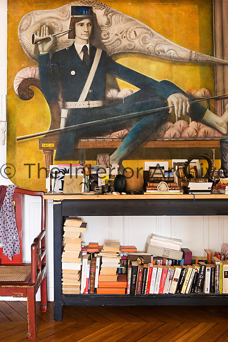 In the living room a vintage painting of a postman is propped on a table laden with a jumble of books and objects