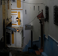 Medina, Tangier, Morocco, pictured on December 27, 2009. A lamplit corner of the Old Town showing a steep staircase outside a cafe whose tiny door is marked by a signpost. Tangier, the 'White City', gateway to North Africa, a port on the Straits of Gibraltar where the Meditaerranean meets the Atlantic is an ancient city where many cultures, Phoenicians, Berbers, Portuguese and Spaniards have all left their mark. With its medina, palace and position overlooking two seas the city is now being developed as a tourist attraction and modern port. Picture by Manuel Cohen