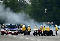 Sept. 1, 2012; Claremont, IN, USA: NHRA safety safari crews put out a fire on the car of top fuel dragster driver David Grubnic during qualifying for the US Nationals at Lucas Oil Raceway. Mandatory Credit: Mark J. Rebilas-