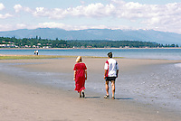 "A Young Couple walking on the Beach at Qualicum Beach, in the ""Oceanside Region"" of Vancouver Island, British Columbia, Canada"