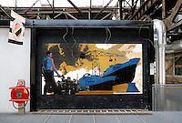 Amsterdam- Noord. NDSM-Werf. In de voormalige werf , waar nu ateliers gevestigd zijn, hangt een muurschildering van een havenarbeider