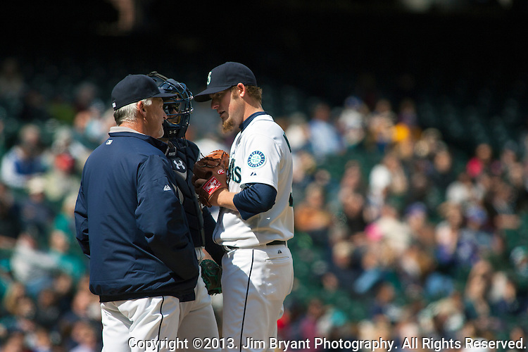 Seattle Mariners' Pitching Coach Carl Willis, catcher Jesus Montero has a conference with starting pitcher Brandon Maurer in the seventh inning April 14, 2013 at Safeco Field in Seattle.  © 2013. Jim Bryant Photo. All Rights Reserved.