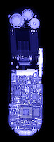An x-ray of a cell phone showing the speakers at the top, and the dense circuitry required to send and receive radio signals.