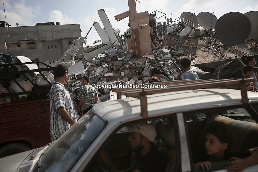 "August 23, 2014 - Gaza City, Gaza strip, Palestinian Territory: Palestinian civilians drive by a house building destroyed as residents collect their goods from the rubble after the building was targeted by an airstrike in the Sabra neighborhood of Gaza City while ""Protective Edge"" Israeli military operation continues in the Gaza strip. (Narciso Contreras/Polaris)"