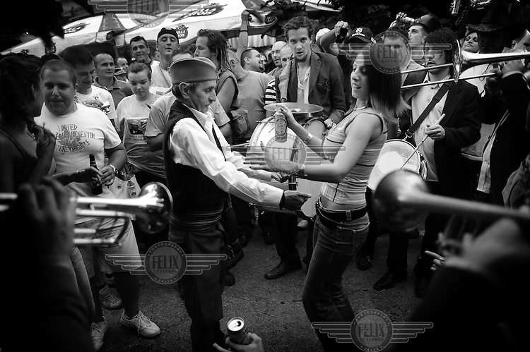 An elderly man dances with a young woman while.a band from Germany plays at the trumpet festival. Hundreds of thousands of visitors gather each year in the small village of Guca for a festival of traditional brass band and folk music, the Dragocevo Trumpet Festival.