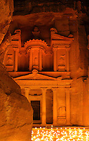 Treasury of the Pharaohs or Khazneh Firaoun, 100 BC - 200 AD, Petra, Ma'an, Jordan. Originally built as a royal tomb, the treasury is so called after a belief that pirates hid their treasure in an urn held here. Carved into the rock face opposite the end of the Siq, the 40m high treasury has a Hellenistic facade with three bare inner rooms. Petra was the capital and royal city of the Nabateans, Arabic desert nomads. Nighttime view with candles lighting up the plaza, seen from the end of the Siq. Picture by Manuel Cohen