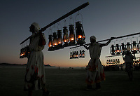 BLACK ROCK CITY,NV - AUGUST 28,2008:  Lamp lighters make their way to the main plaza of Burning Man as the sun sets August 28,2008. Volunteers help in every aspect of the event. The Nevada event, which culminates with the burning of large installation art over the weekend, attracts over 30,000 people annually.