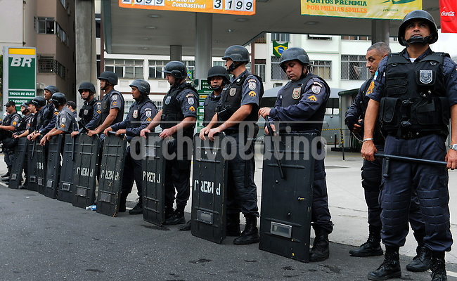 Federal police in riot gear stand guard in a street near Maracana stadium where protesters are gathered in Rio de Janeiro, Brazil, June 30, 2013. Around 4,000 people gathered to denounce corruption, poor public services despite a heavy tax burden, and also the billions of dollars spent to host the World Cup and the 2016 Olympics in Rio - money they say should be going toward better hospitals, schools, transportation projects and schools. (Austral Foto/Renzo Gostoli)