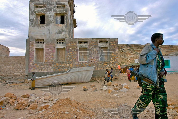 A military guard walks in front of a destroyed building in the coastal village of Eyl. The village is still recovering from the Tsunami in 2004, which destroyed at least 500 fishermen's houses and boats.