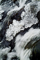 Sections of ice frozen over a fast flowing stream.