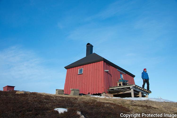 Mann foran Bjørnskardhytta på Varangerhalvøya. ---- Man in front of cabin.