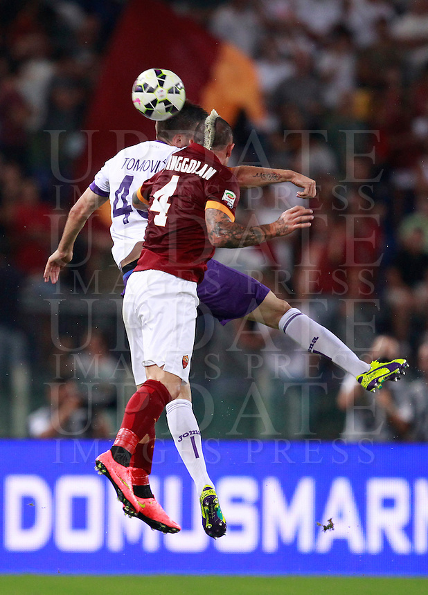 Calcio, Serie A: Roma vs Fiorentina. Roma, stadio Olimpico, 30 agosto 2014.<br /> Fiorentina defender Nenad Tomovic, of Serbia, left, and Roma midfielder Radja Nainggolan, of Belgium, jump for the ball during the Italian Serie A football match between AS Roma and Fiorentina at Rome's Olympic stadium, 30 August 2014.<br /> UPDATE IMAGES PRESS/Isabella Bonotto