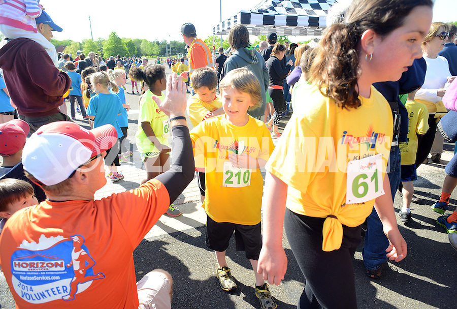 DOYLESTOWN, PA - MAY 18:  Volunteer Bill Hogenauer high fives Nolan Krajewski #210 and Lyla Campbell #61 after they've finished the iRun4Life Kids Only 3k May 18, 2014 at Central Park in Doylestown, Pennsylvania. This is the 5th year of the race in which about 700 runners participated. iRun4Life is a non-profit organization which started in Central Bucks and has 26 elementary schools participating and over 2,200 elementary school runners. (Photo by William Thomas Cain/Cain Images)