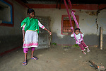 Seuli Tudu swings her daughter Monalisa in the village of Suihari in northern Bangladesh.