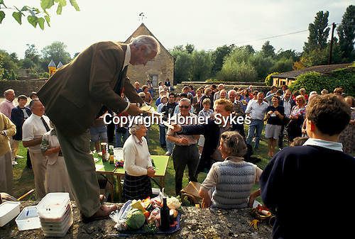 'ENGLISH VILLAGE FETE', DEREK EDWARDS, ONE OF THE ORGANISERS OF THE EAST LEACH TURVILLE VILLAGE FETE, PROCLAIMING THE WINNER OF THE RAFFLE TICKET COMPETITION.