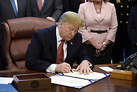 """United States President Donald J. Trump signs S. 1862, the """"Trafficking Victims Protection Reauthorization Act"""" during a in the Oval Office of the White House January 9, 2019 in Washington, DC. Photo Credit: Olivier Douliery/CNP/AdMedia"""
