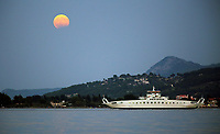 A full moon with a partial eclipse rises, while a ferry boat departs for Eretria in Oropos in the Evia Bay, 30 miles east of Athens, Greece. Monday 07 August 2017