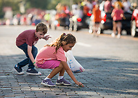 NWA Democrat-Gazette/BEN GOFF @NWABENGOFF<br /> Finn Minardi, 7, of Pea Ridge and Sofia Cortes, 7, of Rogers pick up candy Friday, Oct. 5, 2018, during the Rogers Heritage High homecoming parade through downtown Rogers. This year's parade had a 'Candyland' theme.