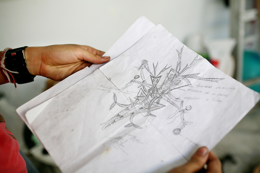 """Natalia Fernandez, 16, looks at a design for her costume, called  """"El Danzante del Sonido,"""" the sound dancer in Spanish, as she makes her costume, at her home in Jayuya, Puerto Rico, on Tuesday, November 18, 2008. Residents will celebrate the 39th annual Festival Indigena de Jayuya, which honors their Taino Indian heritage, this weekend."""