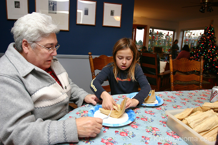 Young Mexican/Italian girl unwraps a tamal for her Mexican American great aunt at a family Tamalada (tamale making party), Torrance, CA