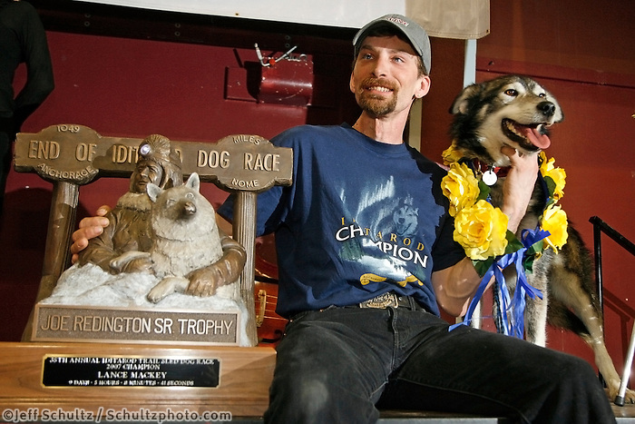 """2007 Iditarod champion Lance Mackey and his lead dog """"Larry"""" pose with the first-place """"Joe Redington Sr."""" trophy at the Nome awards banquet."""