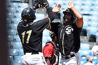 Omaha Storm Chasers outfielder Carlos Peguero (39) is congratulated by Jimmy Paredes (17) after hitting a home run during a game against the Nashville Sounds on May 20, 2014 at Herschel Greer Stadium in Nashville, Tennessee.  Omaha defeated Nashville 4-1.  (Mike Janes/Four Seam Images)