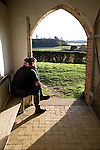 Model released woman sitting in church porch looking at the view over the River Deben, Ramsholt, Suffolk, England