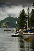 Private jetty at Deep Cove Bay with clouds above the mountains over Mount Seymour provincial park. Deep Cove, Burrard Inlet, Vancouver, British Columbia, Canada.