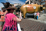 Adrenne Anderson-Smith (L) makes a pictures of tourists infront of a blown up pig at Pikes Place Market in Seattle . Tens of thousands of well-wishers turned out to help celebrate the 100th Anniversary celebration of the market. For a century, the Pike Place Market, has become a city institution and a national attraction, bringing in over a million tourists a year..Jim Bryant Photo. ©2010. ALL RIGHTS RESERVED.