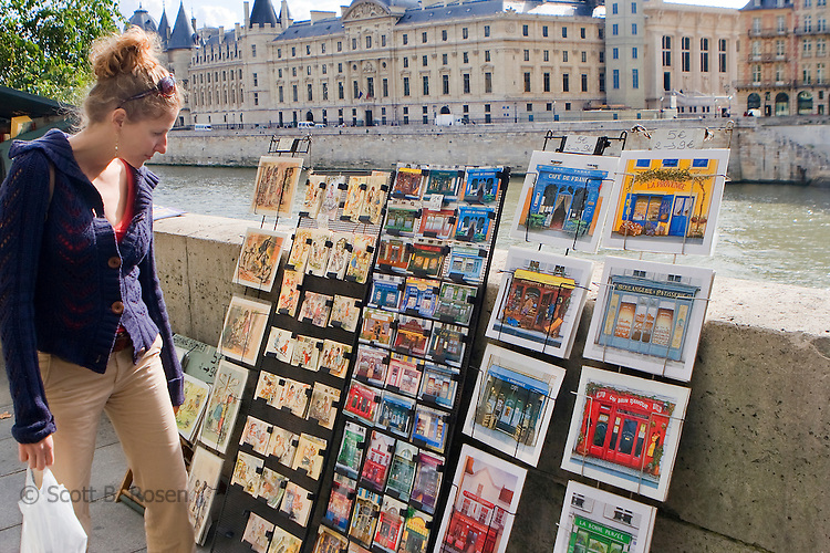 Tourist browses postcards along the river Siene in Paris, France