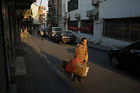 Huanggang, Hebei province, China - An elderly woman carries goods through the old district Dongpo of Huanggang,  October 2014. Famous Song dynasty poet and politician Su Dongpo used to live there in exile.
