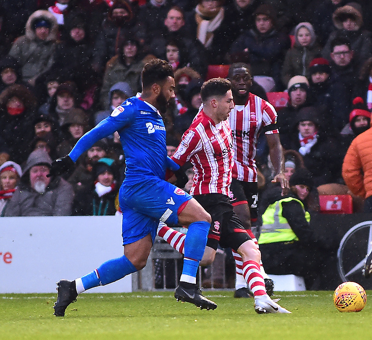 Lincoln City's Tom Pett battles with  Morecambe's Josef Yarney<br /> <br /> Photographer Andrew Vaughan/CameraSport<br /> <br /> The EFL Sky Bet League Two - Saturday 15th December 2018 - Lincoln City v Morecambe - Sincil Bank - Lincoln<br /> <br /> World Copyright © 2018 CameraSport. All rights reserved. 43 Linden Ave. Countesthorpe. Leicester. England. LE8 5PG - Tel: +44 (0) 116 277 4147 - admin@camerasport.com - www.camerasport.com