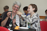 OrigamiUSA 2016 Convention at St. John's University, Queens, New York, USA. Creasers in Leila Torres' Slinky Dog class. Alex Powell (r) helps Jackie Antonoff (l), New York with a fold.