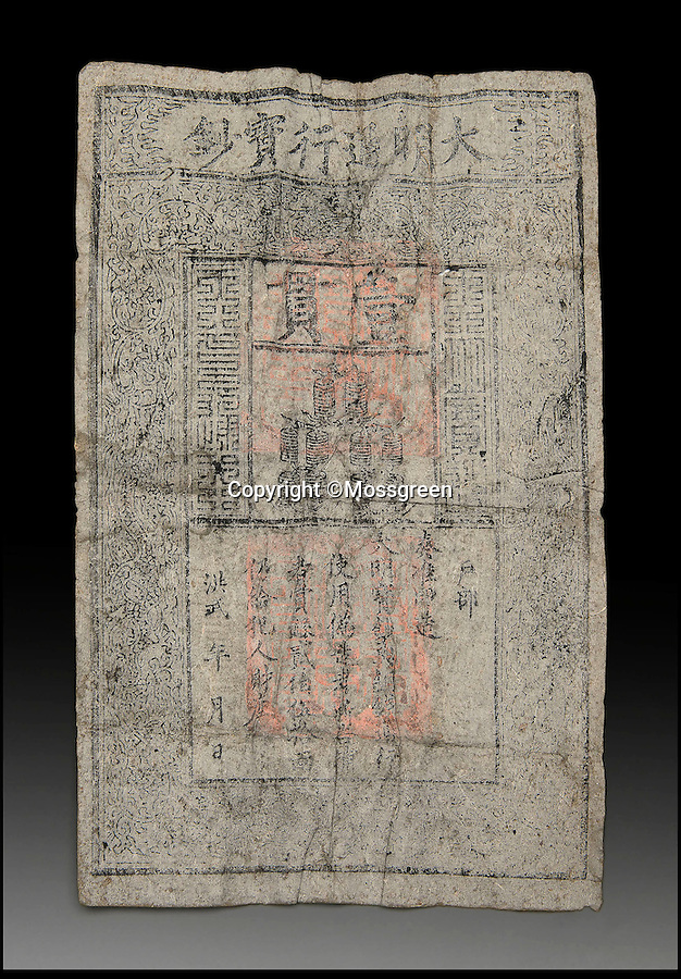 BNPS.co.uk (01202 558833)<br /> Pic: Mossgreen/BNPS<br /> <br /> Not funny money - An ancient Chinese bank note with the grim warning 'those who use counterfeit banknote will be beheaded, the whistle-blower will be rewarded 250 Liang silvers plus all the properties of the criminal.' has been discovered in an old buddhist statue.<br /> <br /> A rare 700-year-old Chinese banknote dating from the Ming Dynasty has been discovered hidden inside the head of an ornamental Buddhist monument. <br /> <br /> The crumpled A4-sized piece of paper was found in a 13th century wooden sculpture of a Luohan - a name given to those who have achieved enlightenment - purely by chance at an auction house in Australia. <br /> <br /> Specialists were inspecting the carving for any damage so that it could be valued before going under the hammer when they uncovered the folded currency concealed in the head cavity.<br /> <br /> The Luohan sculpture and the banknote will be be sold together next month by Mossgreen auction house in Australia with a combined estimate of £37,000. The banknote on its own would be expected to achieve £3,000.