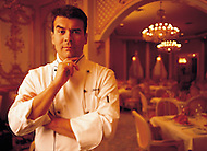 A chef stands in the dining room of his upscale restaurant