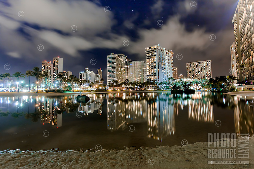 Duke Kahanamoku Lagoon at night, with hotels and their lights reflected in the lagoon's waters, Waikiki, O'ahu.