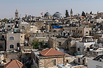 A  view of the Christian Quarter in the Old City of Jerusalem from the ramparts of the city wall on the north.  Left to right is the bell tower of the Lutheran Church of the Redeemer, with the grey domes of the Church of the Holy Sepulchre in the center.  Next is the minaret of the Mosque of Omar ibn Al-Khattab.  The Israeli flags are flying on the top of the Tower of Phasael in the Citadel or Tower of David.  The gold dome is the Greek Orthodox Church of Saint John the Baptist.   The Old City of Jerusalem and its Walls - UNESCO World Heritage Site