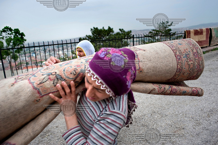 A woman, assisted by her mother, carries a freshly washed carpet along a road where it has been drying on a railing.